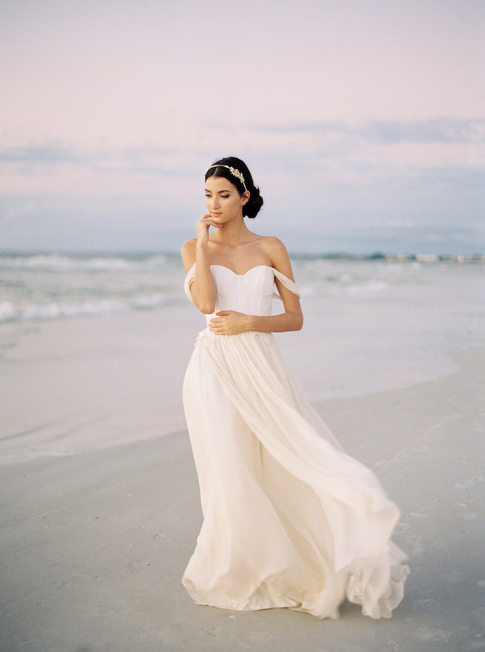 flowy white dress, with slouched shoulder straps, worn by young woman, with dark hair tied back, and silver tiara, beach wedding at sunset