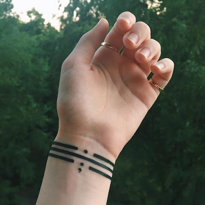 semicolon project tattoo, three black stripes, around a person's wrist, one punctuated by a full stop, on punctuated by a semicolon, and one unpunctuated