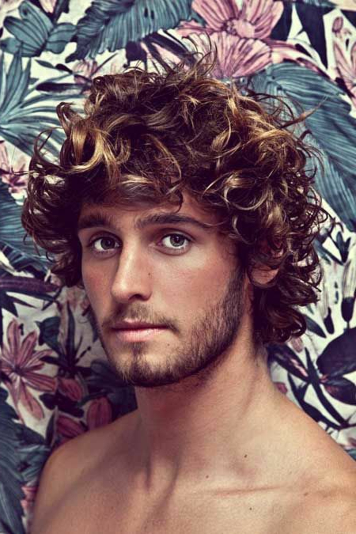 surfer curls in brown, with dark blonde highlights, on topless man, with short beard and mustache, hairstyles for short curly hair, tropical flower wallpaper behind him