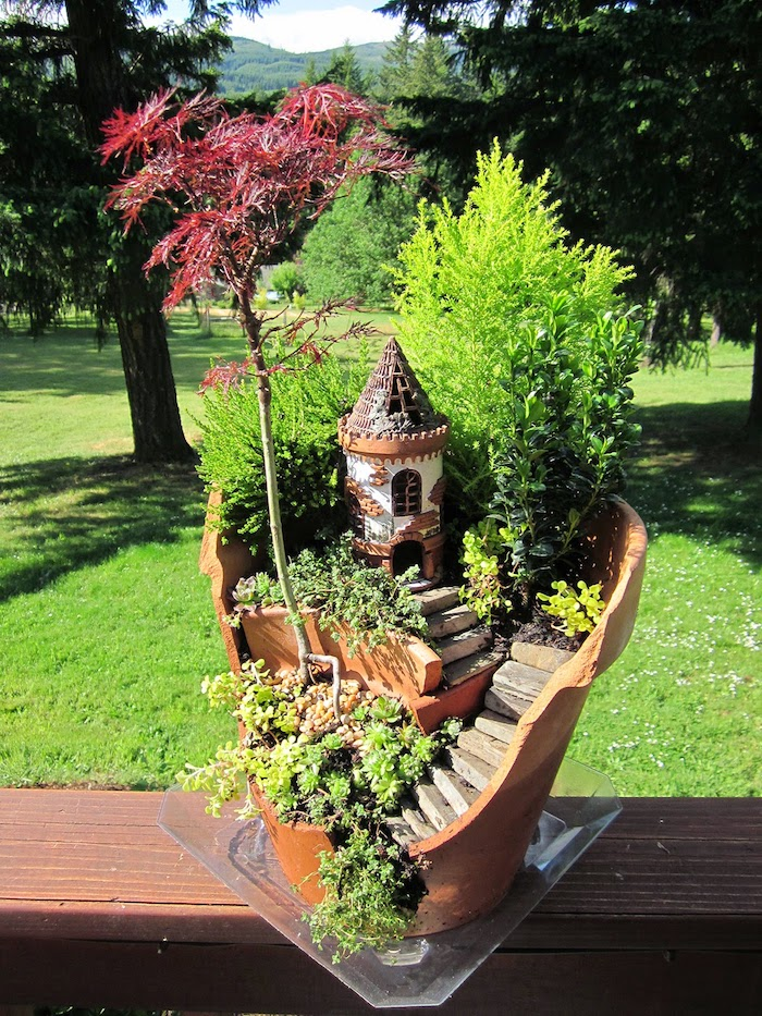 castle fairy tower, made from painted plaster or clay, inside a broken ceramic pot, with little stairs, bonsai tree and shrub, various tiny green plants