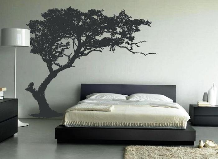silhouette of a tree, painted in black on a pale gray wall, large wall art, near black bed with matching cupboards, pale gray lamp, beige fluffy rug