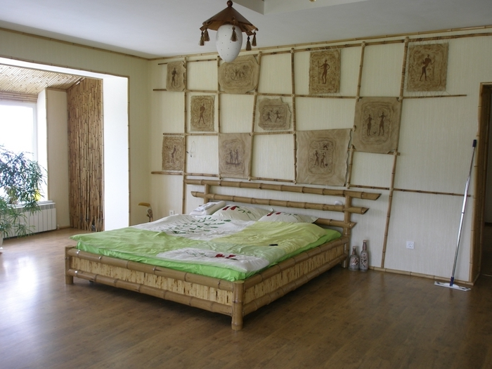 parchment pieces in beige, covered in brown tribal drawings, hung on bamboo poles, on a cream wall, near asian-inspired bamboo bed