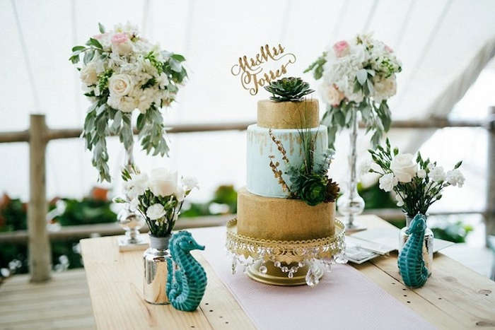 gold and pale blue wedding cake, decorated with succulents, on a wooden table, with two seahorse statuettes, and four vases, containing bouquets of different sizes