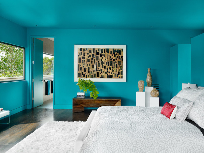bedroom design, turquoise colored walls and door, large framed abstract painting, double bed and fluffy rug, dark laminate floor