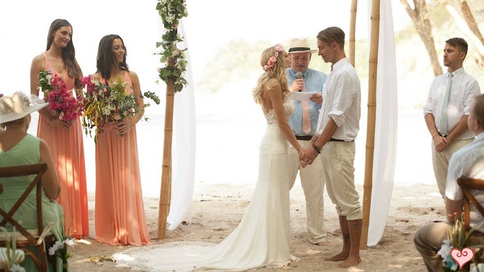 casual nuptials ceremony, an example of beach weddings in florida, two bridesmaids in peach colored maxi dresses, holding large bouquets, blonde bride in white gown, barefoot groom in light relaxed clothing