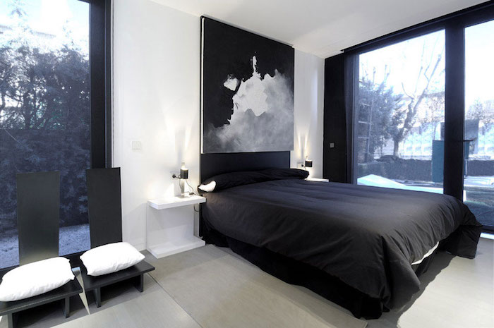 black and white bedroom design, with white walls, two black chairs with white cushions, black bed and window frames, large artwork in gray, black and white