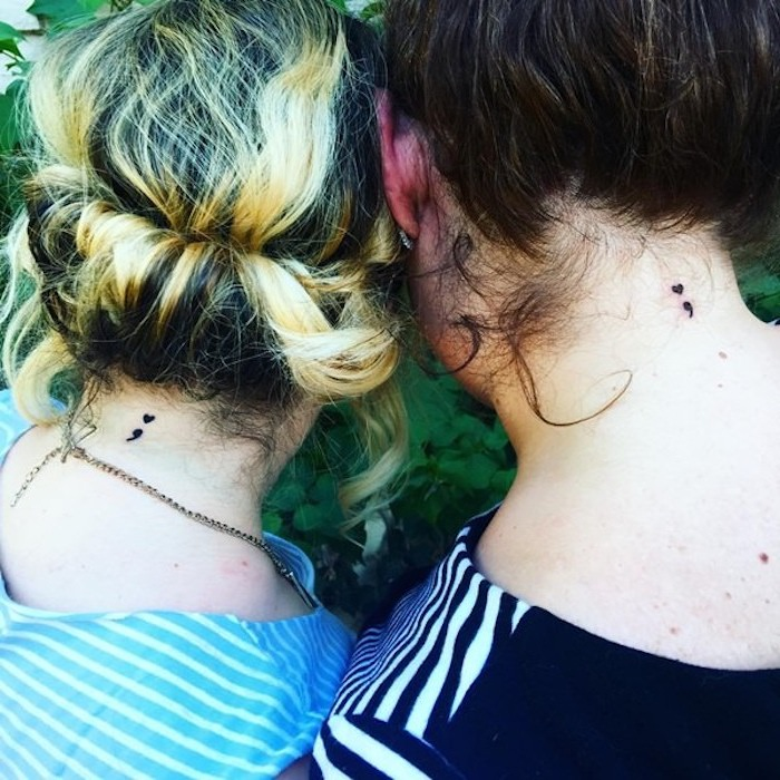 friendship matching tattoos, on the back of the neck, semicolon movement tattoos, worn by two women, with hair tied up, blonde and brunette