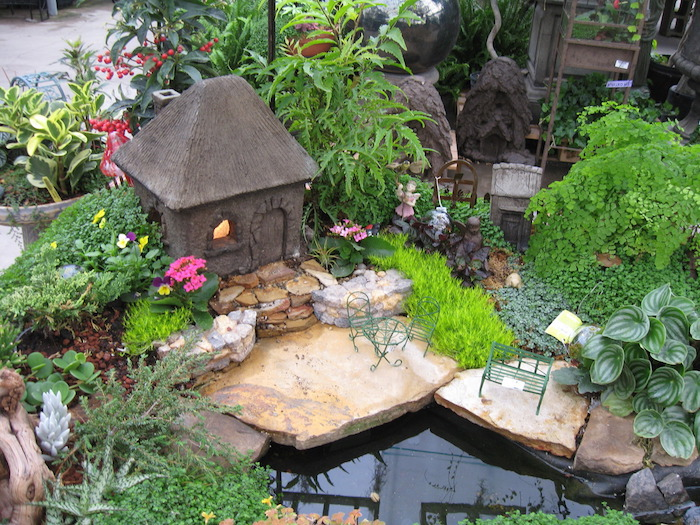 artificial pool surrounded by stones of various sizes, in a garden with many different kinds of green plants, decorated with miniature fairy house made of stone, a tiny bench, and a small table with matching chairs