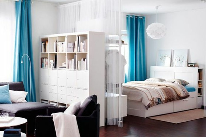 small apartment ideas, blue blackout and white sheer curtains, inside a studio flat, with bed and sofa, white cupboard and dark brown wooden floor