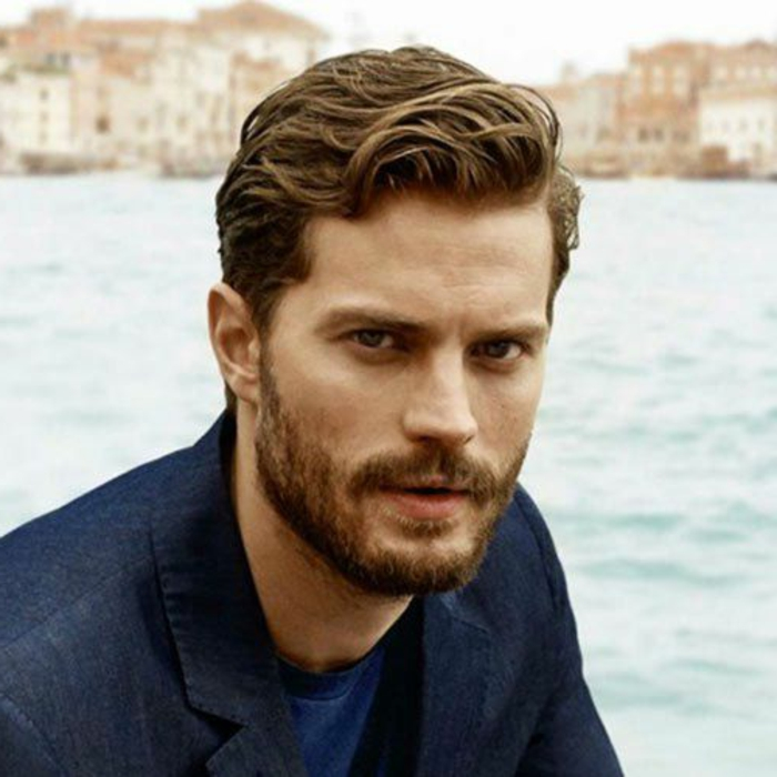 jamie dornan with wavy, short hair and bangs combed over to one side, beard and mustache, dark denim blazer and blue t-shirt