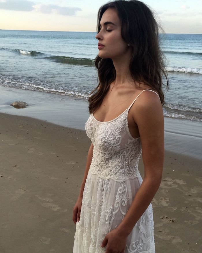 strappy white maxi dress, with embroidery and sequins, on a young tanned brunette woman, with closed eyes and wavy hair, standing on the seashore