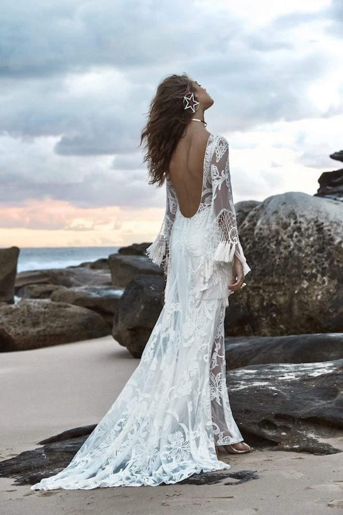 big hoop earring, with star-shaped decoration, worn by tan brunette woman, beach wedding, white lace boho gown, with tassels and sheer details, and cutout back