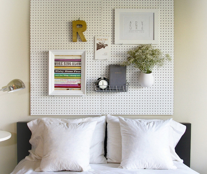 small flower vase with white flowers, two framed images, wire shelf with book and alarm clock, attached to a white board, hanging over a double bed, bedroom design