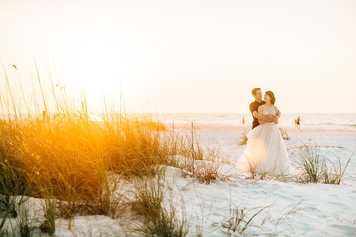 plants growing on a white sandy beach, a casually dressed man, hugging a woman in long white bridal gown, beach weddings in florida, sea and a sunset in the background