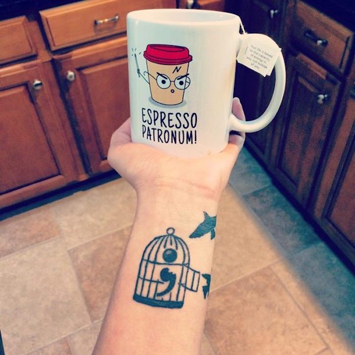 birdcage with open door, containing a semicolon, tattooed on a person's arm, near two birds in flight, hand holds a white mug, with a comical cartoon and message, semicolon tattoo on wrist