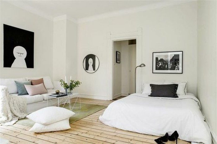 square and round artworks in black and white, inside minimalistic room, how to decorate a studio apartment, pale wooden floor, sofa and bed in white