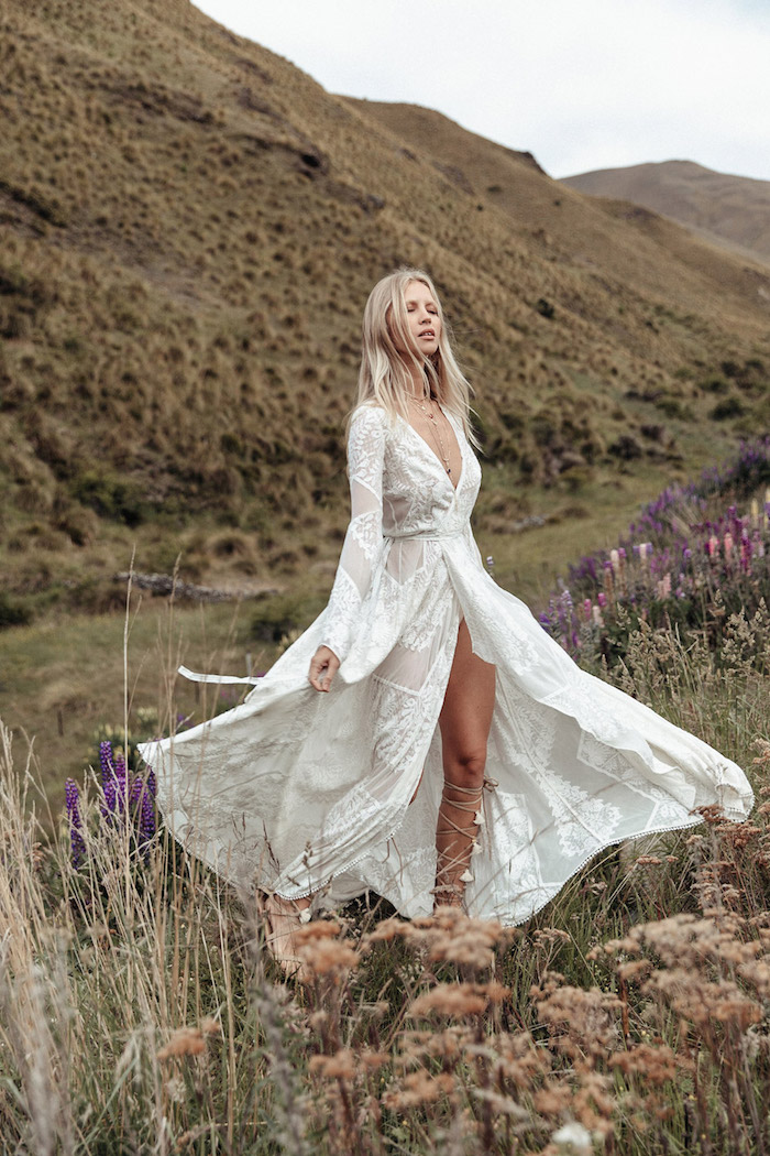 wrap-around white dress, with long sleeves and embroidery, on blonde woman, with closed eyes, wearing lace up gladiator sandals, beach wedding, wild flowers on a field