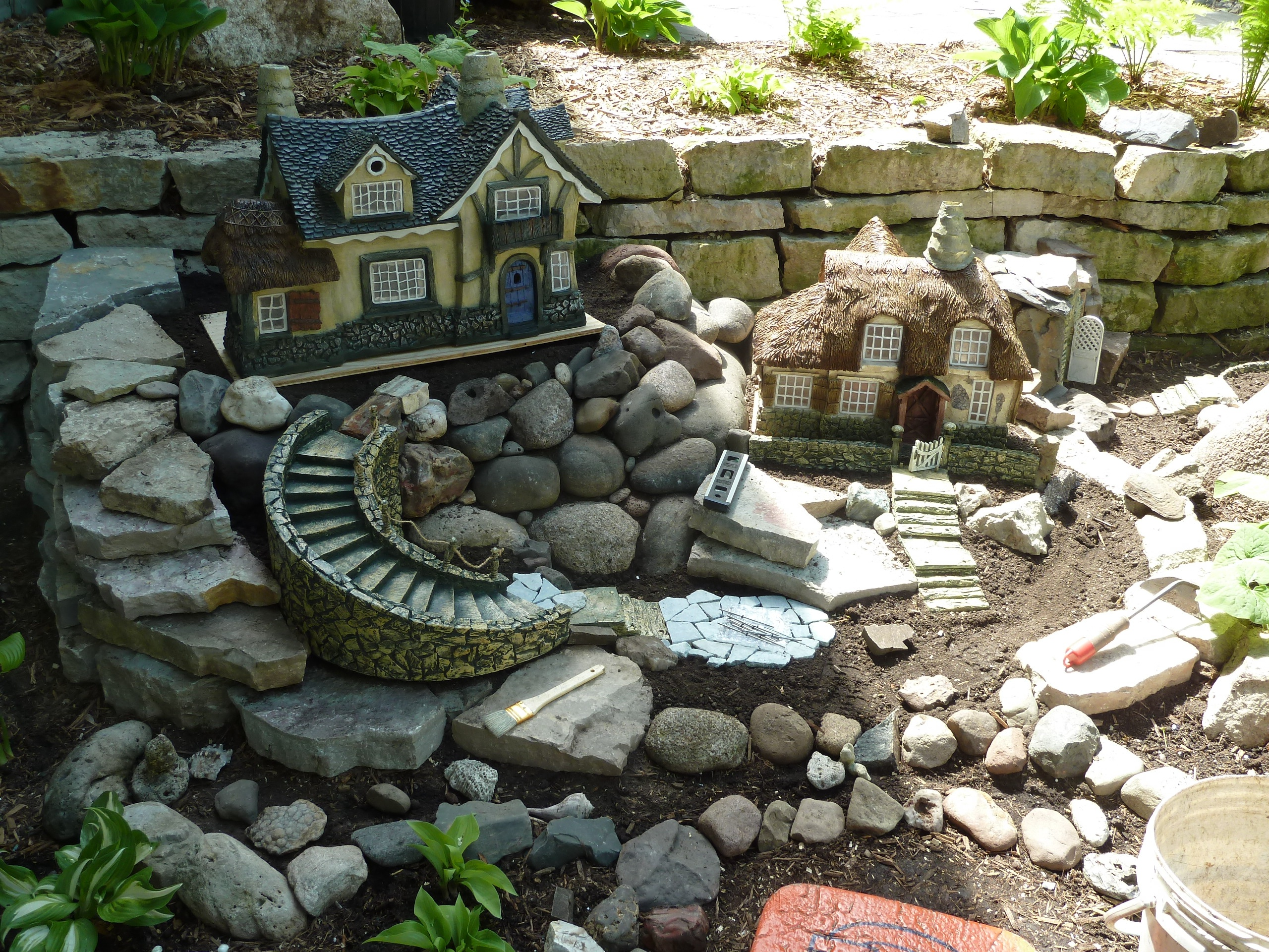 fairy garden pictures, garden with lots of gray stones of different sizes, decorated with two miniature houses, several green plants and tools