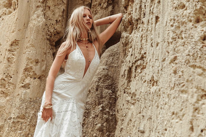 platinum blonde woman, wearing a white lace boho wedding dress, with several necklaces and bracelets, beach wedding attire, leaning on a pale beige rock