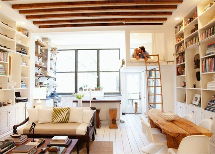 compact one-room flat, with kissing couple in a mezzanine bed, studio apartment ideas, asymmetrical wooden dining table, with white chairs, sofa and many filled bookshelves