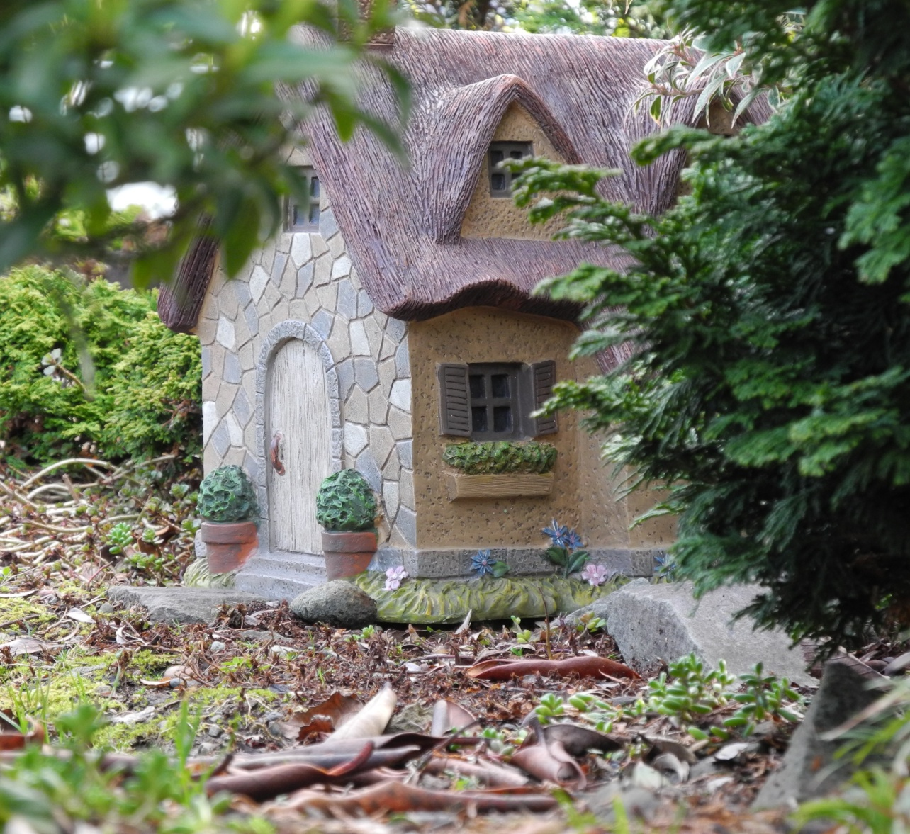 house-shaped garden decoration, made from ceramic or moulding clay, placed on a forest floor, diy fairy house, near green shrubs and branches