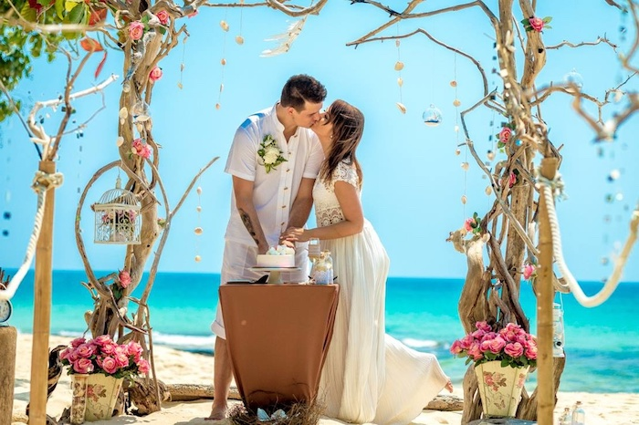 lots of pink roses, and a wedding arch formed by intertwining trees, on a white sandy shore, near an azure blue sea, beach wedding venues, kissing bride and groom