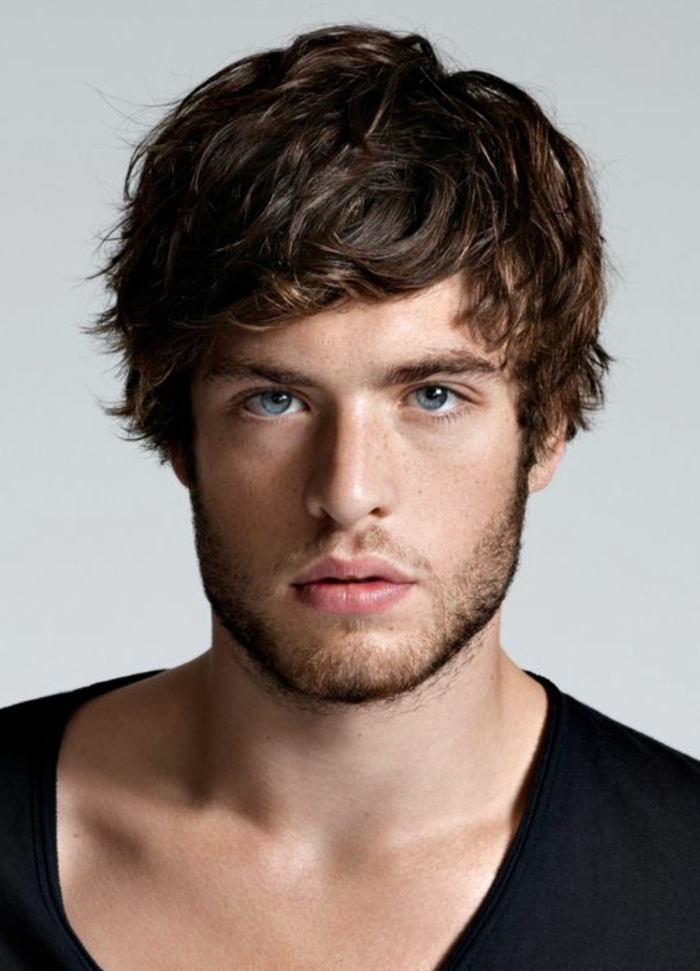 boyish layered haircut, with wavy bangs falling on the forehead, guys with curly hair, blue-eyed man with short beard, wearing a black slouchy top