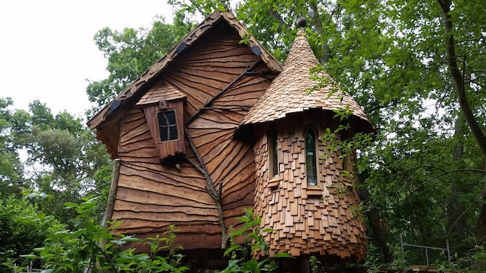 unusual wooden house, with asymmetrical features, covered with wooden planks and tiles, several windows and a tower-like feature