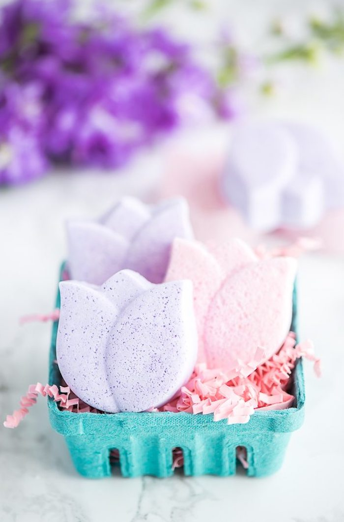tulip diy bath bombs, in pale violet, and light pastel pink, placed on pink easter grass, inside a teal blue cardboard box