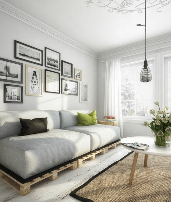 nordic style room, with white floor, walls and ceiling, containing a modern coffee table, a diy pallet sofa, a beige rug, and a hanging lamp