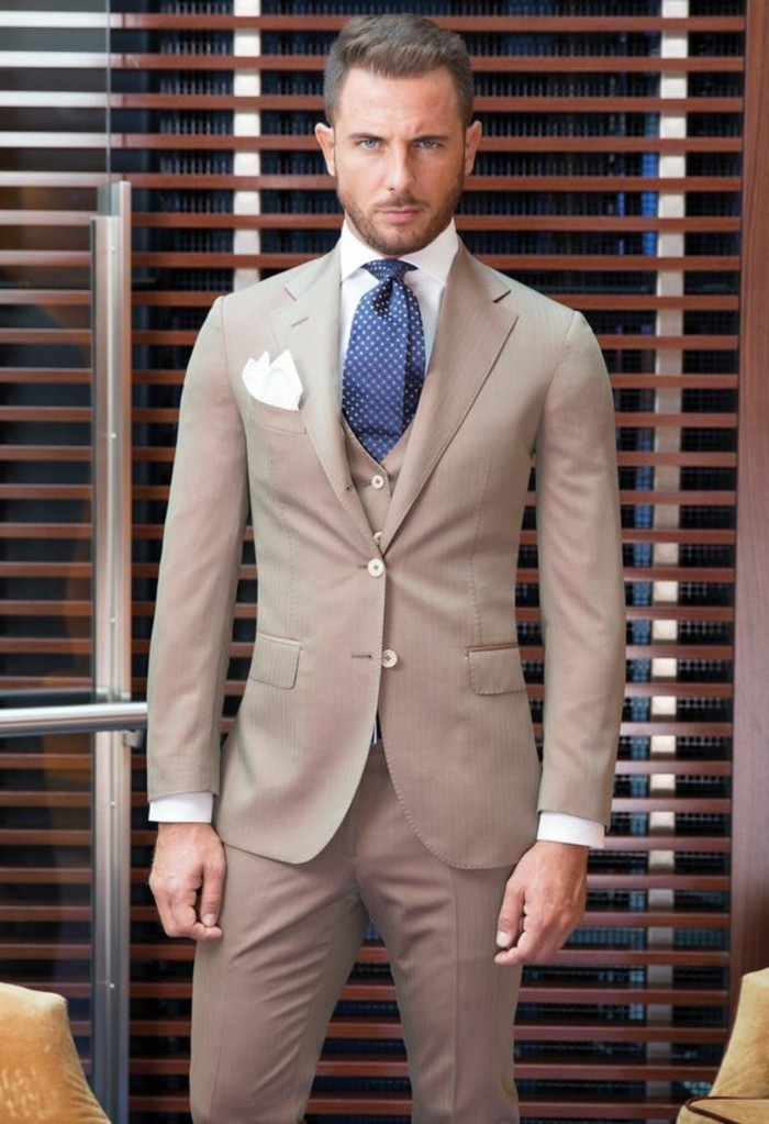 tight-fitting three piece suit in beige, worn with a white shirt, dark blue patterned tie, and a white pocket handkerchief, how to dress for a wedding male, serious looking man
