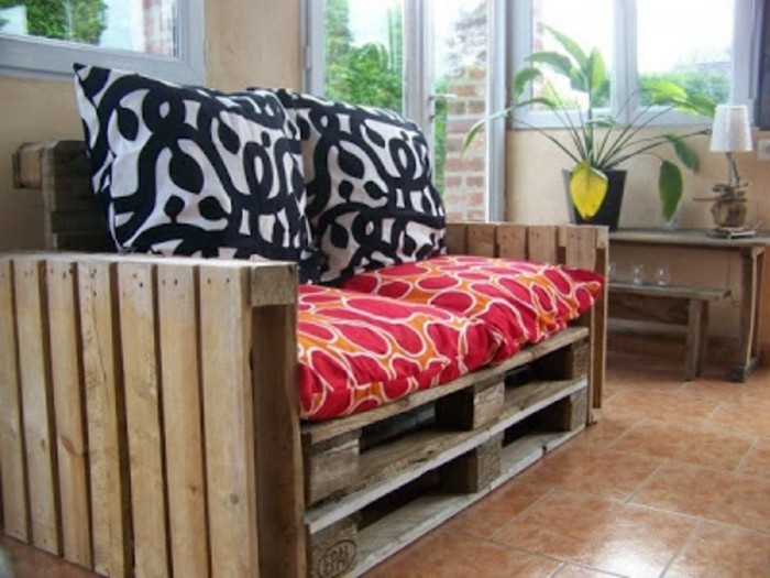 cushions in black and white, and orange and red, decorating a diy sofa, made from wooden pallets, inside a bright room, with a small table and potted plant