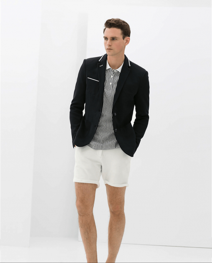 black blazer with white details, worn over striped white and black shirt, and white shorts, garden party attire, on a young brunette man, with hands in his pockets