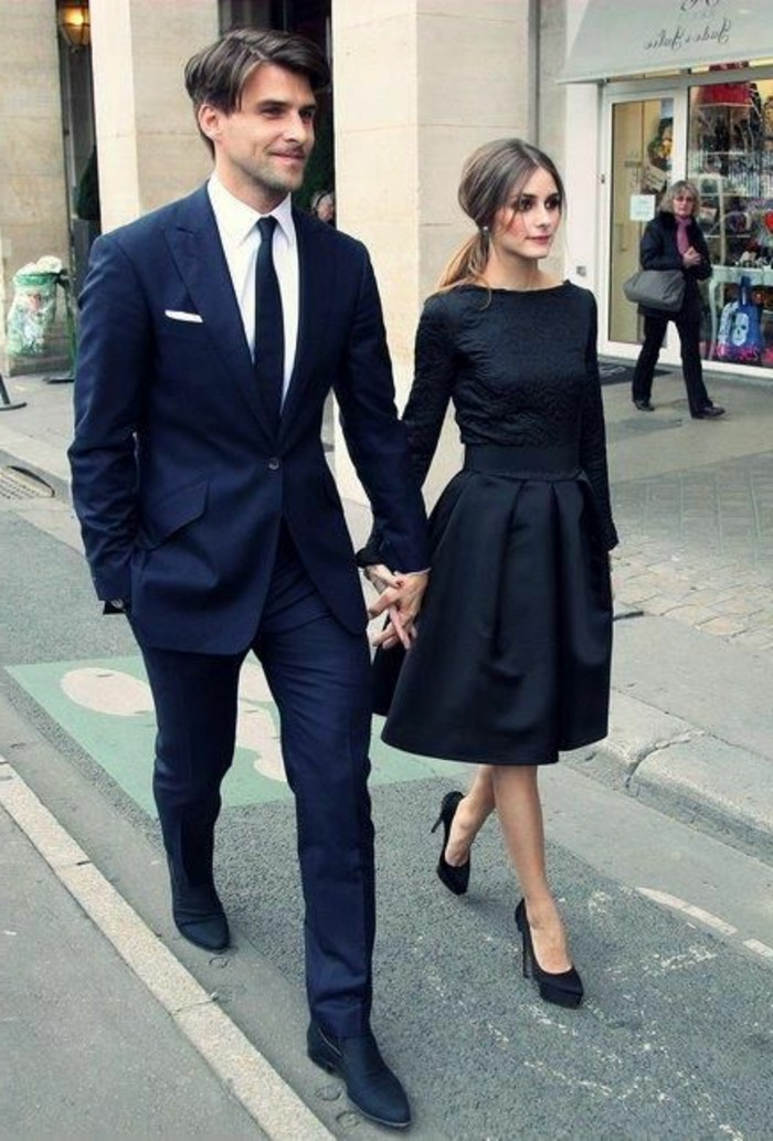sharply dressed couple walking hand in hand, dark blue suit, white shirt and black tie, black retro midi dress, with long sleeves, black tie attire for men