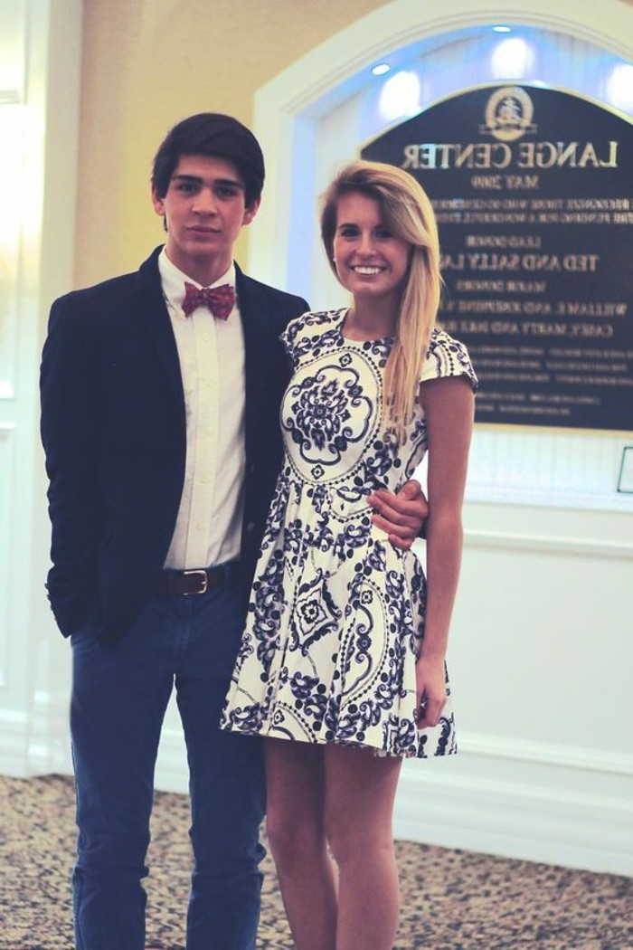 what is cocktail attire for men, young brunette man, wearing dark blue jeans, white shirt with red bowtie, and a black blazer, with his arm around a smiling blonde woman