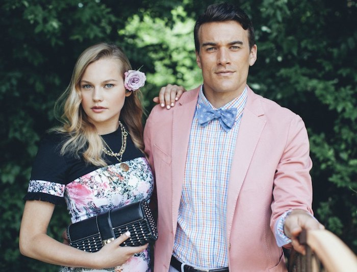 dressy casual men, blonde woman in black top, with floral details, leaning on man in pale pink blazer, worn over white, pale pink and pale blue checkered shirt, wit blue patterned bowtie