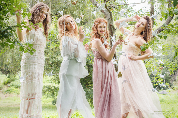 crochet lace dress in white, floaty pale blue gown, pink maxi dress, and white tulle dress with lace, worn by four young women, dressy casual style, boho tea party
