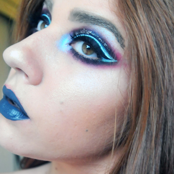 layered eyeshadow in black, pink and different shades of blue, decorated with glitter, worn by woman with blue lipstick