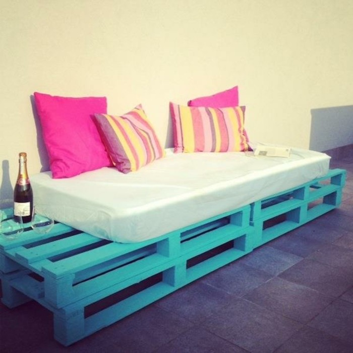 mattress in white, covering a settee made from pallets, painted in a turquoise color, and decorated with two sets of cushions, fuchsia pink and striped, pallet patio furniture, bottle of champagne with two glasses