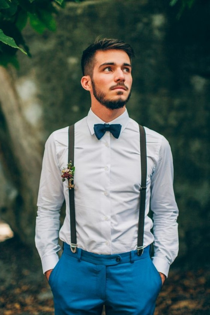 suspenders with a boutonniere, worn with a blue shirt, and teal blue trousers, mens wedding guest attire, on young man with a bowtie