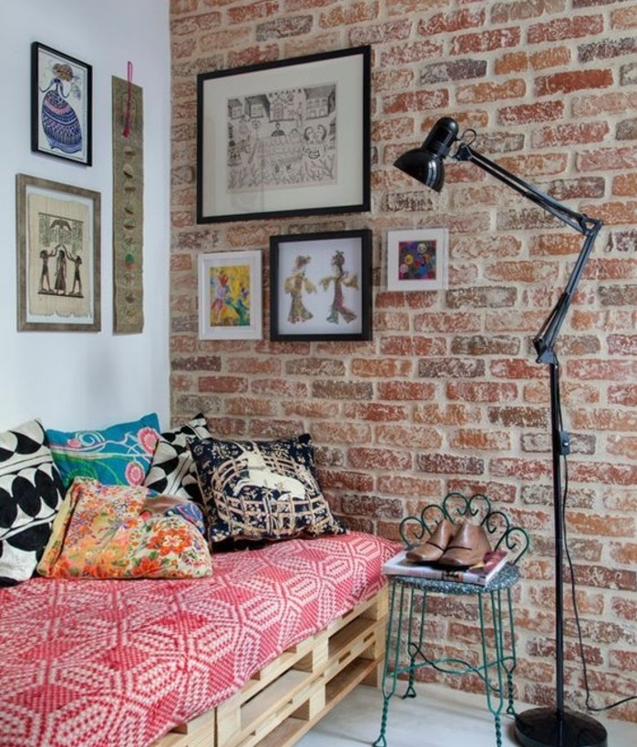 several artworks decorating a room with one white wall, and one brick wall, containing a pallet settee, with lots of cushions, how to make pallet furniture, tall lamp and a vintage chair