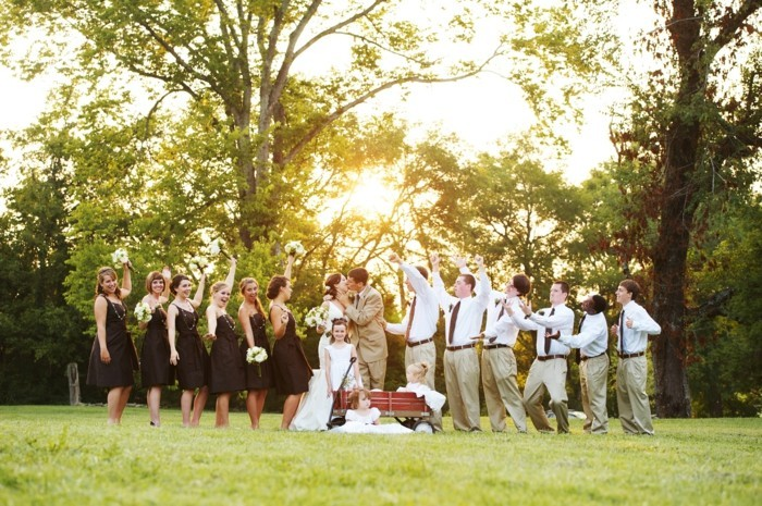 wedding photo on a green lawn with trees, bride and groom kissing, flower girls and bridesmaids, six men in coordinated outfits, how to dress for a wedding male, white shirts and beige trousers