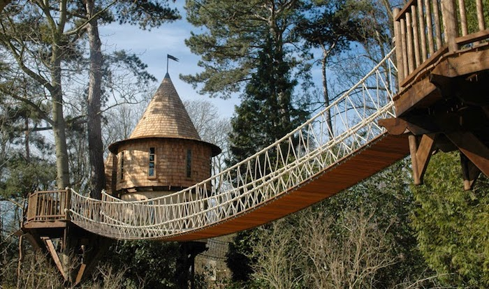 tower-like structures linked together through a bridge, made from rope and wooden planks, diy treehouse, situated in a forest