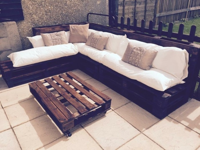 coffee table made from dark wooden pallets, near matching sofa, covered in white pillows, and decorated with beige patterned cushions, pallet outdoor furniture, on a tiled terrace