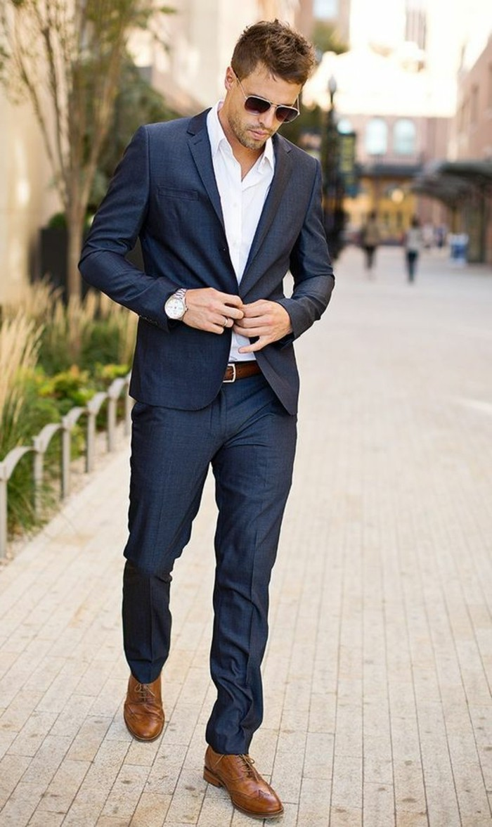walking man dressed in a dark blue suit, with white shirt, and brown brogue shoes, wearing sunglasses and a wrist watch