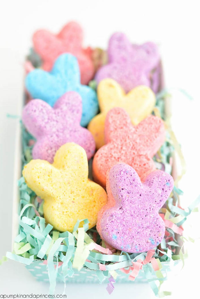 rabbit shaped bath bombs, in different pastel colors, placed in a plastic box, filled with multicolored easter grass, cartoon bunny heads