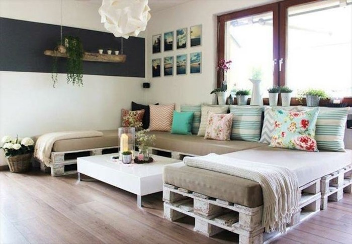 pallet couch shaped like a c, covered with beige foam mattresses, and decorated with lots of cushions, in different sizes and colors
