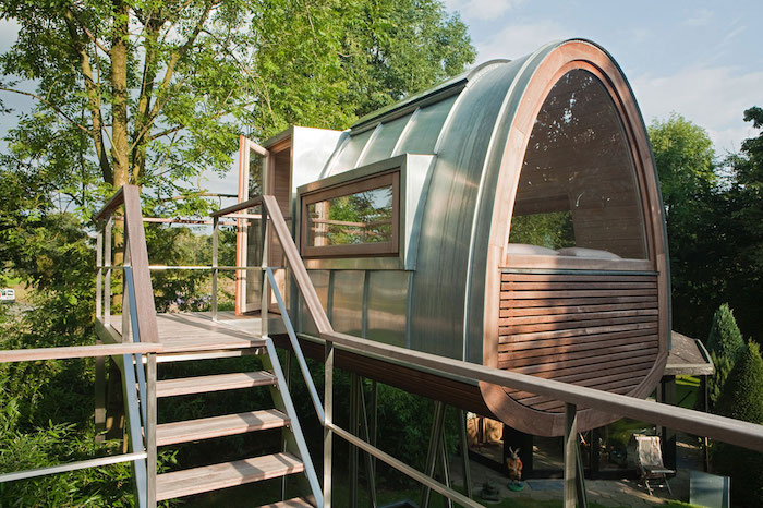treehouse designs, modern structure made of wood and metal, with several windows, built on a platform above the ground, near several green trees