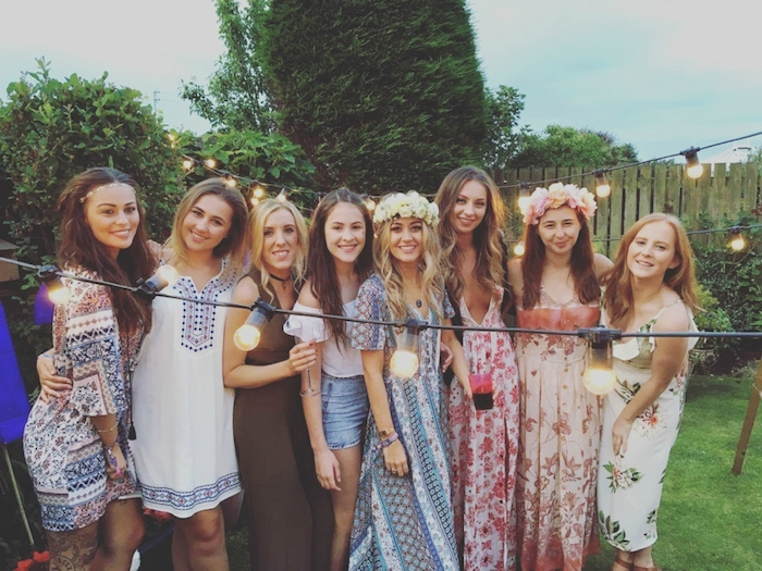 eight young women, dressed in multicolored patterned maxi dresses, folk-inspired boho tunics, denim shorts and a white top, casual dress code, smiling and posing for a photo