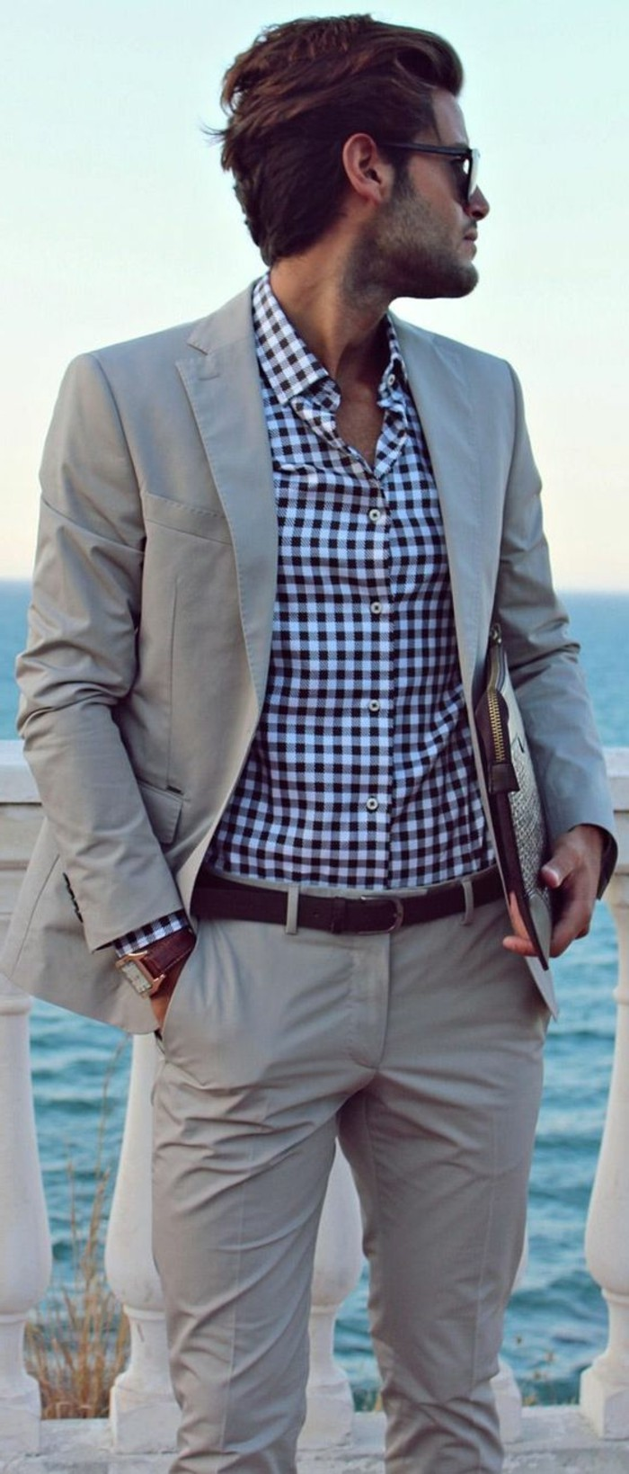 beige two piece suit, worn with blue and white checkered shirt, by brunette man, mens casual summer wedding attire, with glasses and a hand in his pocket